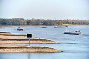 Nederland, the netherlands, Nijmegen, 16-10-2018Binnenvaartschepen varen in de Waal langs de oever en de ooijpolder. Door de aanhoudende droogte staat het water in de rijn, ijssel en waal extreem laag .Laagterecord en de laagste officiele stand ooit bij Lobith gemeten, 6,73 m boven NAP . Schepen moeten minder lading innemen om niet te diep te komen . Hierdoor is het drukker in de smallere vaargeul . Door te weinig regenval in het stroomgebied van de rijn is het record verbroken .Foto: Flip Franssen
