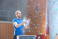 Confident man dusting powder by climbing wall in crossfit gym