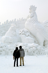 Visitors to Harbin Snow Sculpture Festiva looking at large rooster carved from snow China 2005