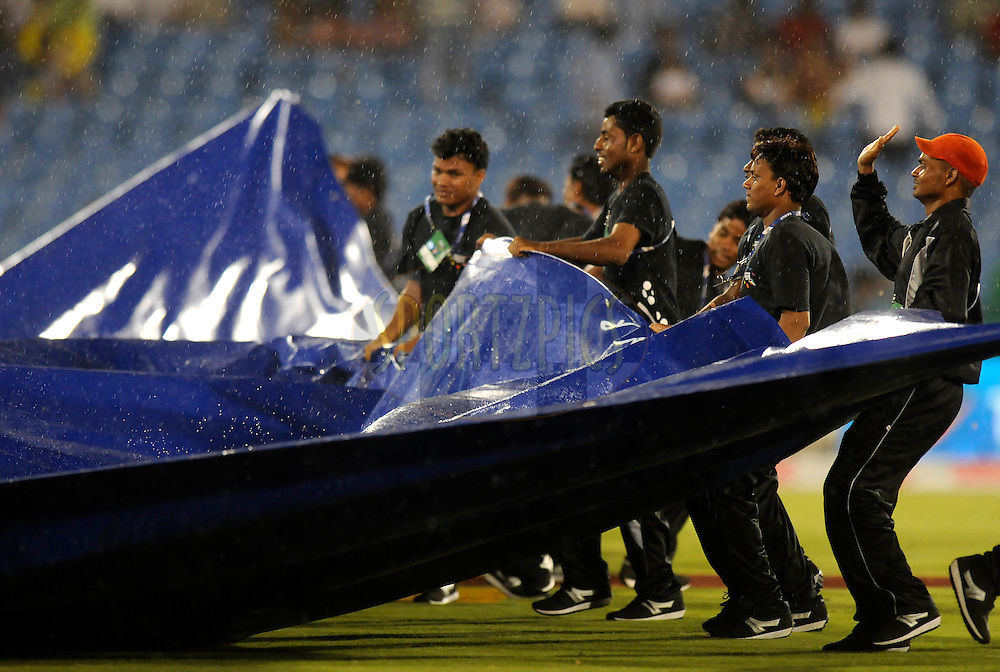 Grounds men are seen at work as rain stops the play during match 3 of the Oppo Champions League Twenty20 between the Cape Cobras and the Northern Knights held at the Chhattisgarh International Cricket Stadium, Raipur, India on the 19th September 2014<br /> <br /> Photo by:  Pal Pillai / Sportzpics/ CLT20<br /> <br /> <br /> Image use is subject to the terms and conditions as laid out by the BCCI/ CLT20.  The terms and conditions can be downloaded here:<br /> <br /> http://sportzpics.photoshelter.com/gallery/CLT20-Image-Terms-and-Conditions-2014/G0000IfNJn535VPU/C0000QhhKadWcjYs