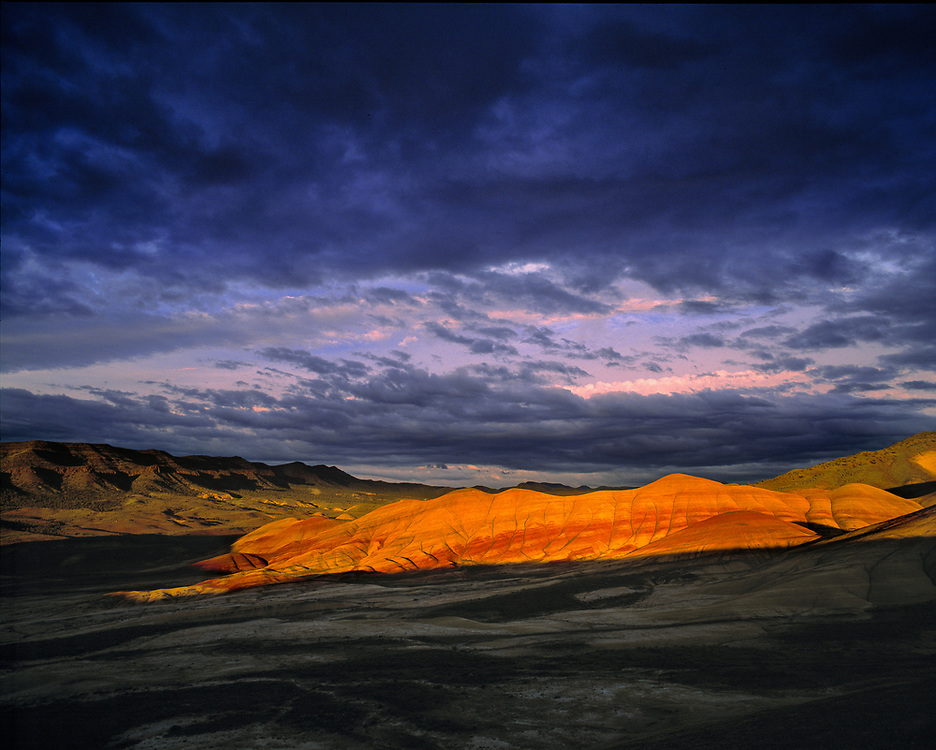 Parting clouds highlight the Painted Hills at sunset at John Day Fossil Beds National Monument in Oregon. ©Ric Ergenbright