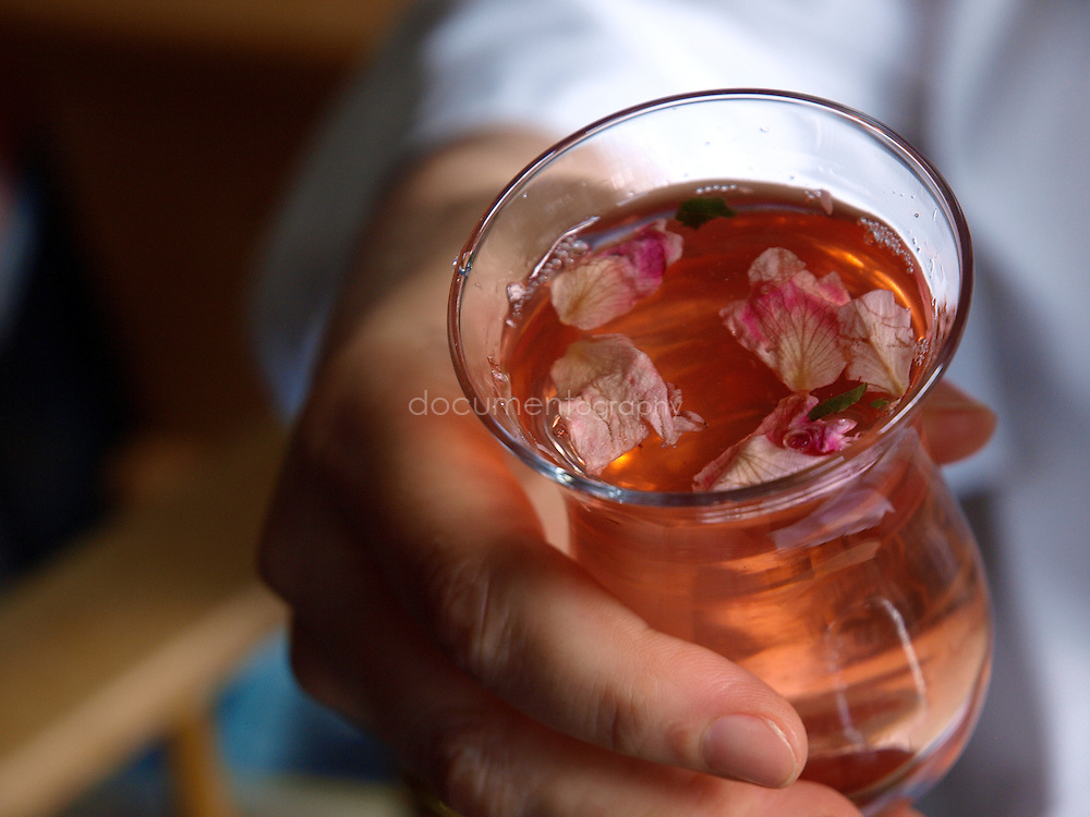 Lebanese Chef Anissa Helou holds a glass of rose sherbet at the house of her friend, Palestinian singer Reem Kelani, London.