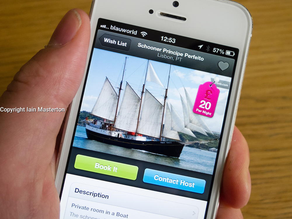 Using Airbnb app to book holiday accomodation on a sailing ship with a white iPhone 5 smartphone