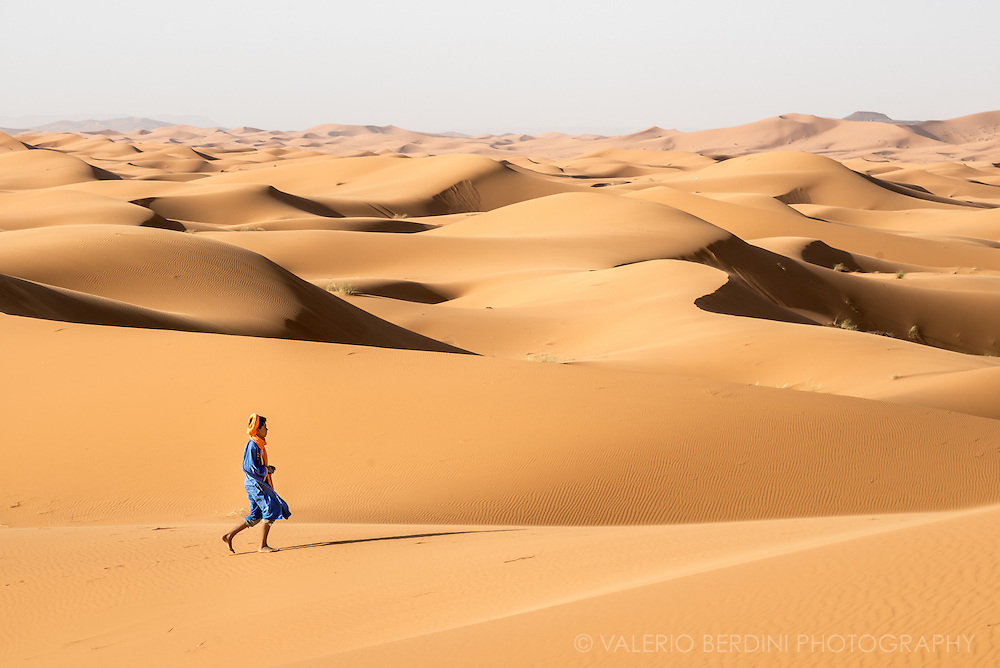 A young berber man, in his colourful dress and turban (tagelmust), takes an early morning walk among the sand dunes of the Sahara desert in Erg Chebby in Morocco. Despite their similarity and their shape constantly modelled by winds, the berbers living in the desert can easily find their way among the dunes.