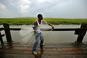 Casting for bait off a state owned dock, Brandon Dixon fishes the creeks about Sapelo Island, Ga. The residents, whom many are decedents of slaves, share the island with Department of Natural Resources and the University of Georgia. Much of the infrastructure such as boat docks, paved roads and fire equipment are provided by state college or agency. (Stephen Morton for The New York Times)