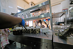 JOHANNESBURG SOUTH AFRICA - MAY 01 Hudsons Parkhurst staff prepare food for delivery on May 01, 2020 in Johannesburg South Africa. South Africa moved down to Level 4 of the national lockdown with relaxed restrictions as part of a risk adjusted 5 stage phasing of lockdown measures. This includes allowing of certain restaurants to reopen for trade and prepare hot food as delivered takeaway only. (Photo by Gallo Images/ Dino Lloyd)