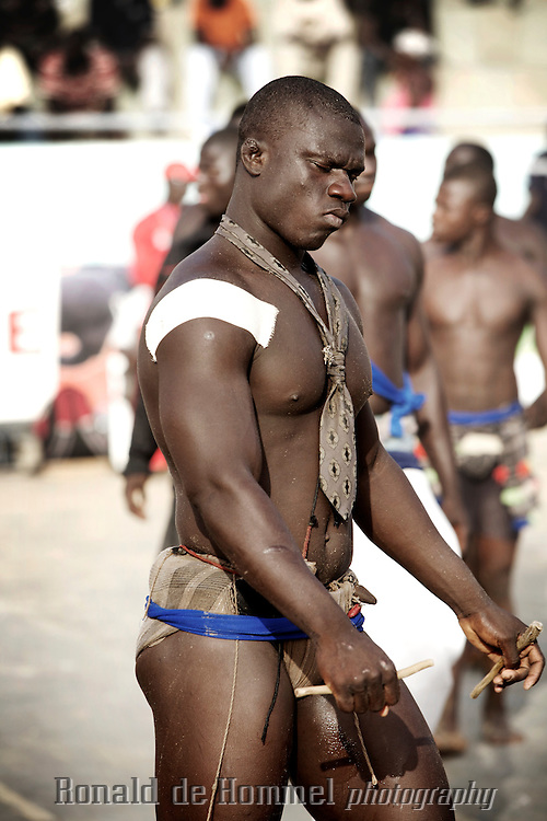 African traditional wrestlers prepare for their match in the international championship of The Economic Community Of West African States (ECOWAS or CEDEAO) in Dakar Senegal. After losing the title to Nigeria last year, the Senegalese home team came out as champion again this time. The championship is prestigious, but commercial wrestling where the fighters are allowed to punch (lutte avec frappe) is more popular with audience and players. The prize money in those fights goes up to 150.000 Euros. The matches attract up to 60.000 spectators. Wrestling has become more popular than football in Senegal in recent years.