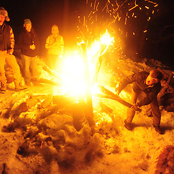 Revelers are warmed by the fire under a full moon in the mountains of western New Mexico