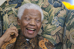 Former South African President Nelson Mandela laughs during his meeting with Conservative Party leader David Cameron at The Dorchester in central London.