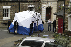 © Licensed to London News Pictures. 08/04/2016. London, UK.  Police move a forensics tent into place in front of a bin cupboard near Block E on the Peabody estate where local residents claim the body of missing policeman Gordon Semple was found. A man was arrested yesterday. Photo credit: Peter Macdiarmid/LNP