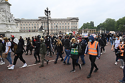 © Licensed to London News Pictures. 12/06/2020. London, UK. Protestors pass Buckingham Palace during a Black Lives Matter demonstration In  central London. Black Lives Matter have called for the removal of statues from throughout the UK of historical characters involved in the slave trade, following the death of George Floyd in the U. S. A . Photo credit: Ben Cawthra/LNP