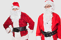 Young men in Santa costume standing against gray background
