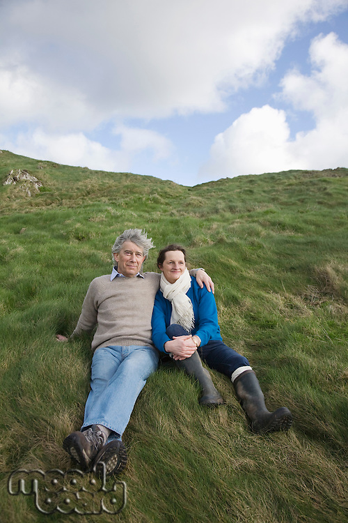 Mature couple sit full lengtgh on a hillside