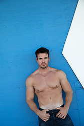 shirtless hot guy against a painted wall