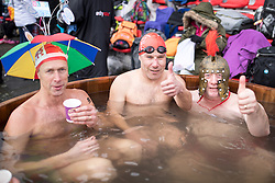 © Licensed to London News Pictures. 28/01/2017. London, UK. Swimmers who have competed in the 'Best Hat' competition relax in the hot tub at the 7th UK Cold Water Swimming Championships, taking place at Tooting Bec Lido. Ice in the Lido has only recently thawed following freezing temperatures in London over the past week. Temperatures in the pool today at 1 degree celsius. Photo credit : Tom Nicholson/LNP