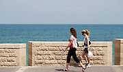 Israel, Tel Aviv-Jaffa, Two women walking on the beach front promenade
