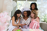Bride showing engagement ring to friends at bridal shower