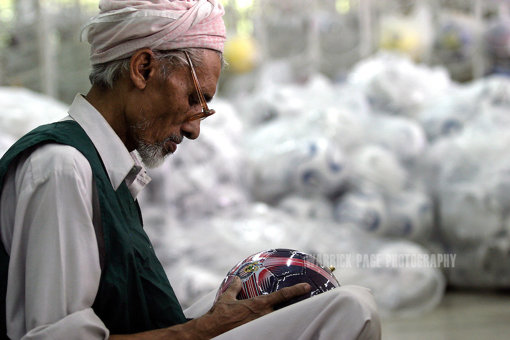 SIALKOT, PAKISTAN - JUNE 7: A worker at the Sublime sporting goods factory stitches together football panels June 7, 2006 in Sialkot, Pakistan. Sialkot is the world's largest supplier of footballs and has shipped over 55 million ahead of the FIFA World Cup in Germany, beginning Friday June 9, 2006. Sialkot is home to dozens of sporting goods factories and made headlines in 1997 when it was discovered child labour was widely used in football manufacturing. Local and international pressure forced companies to reform and phase out the use of children in their workplace. (Photo by Warrick Page)