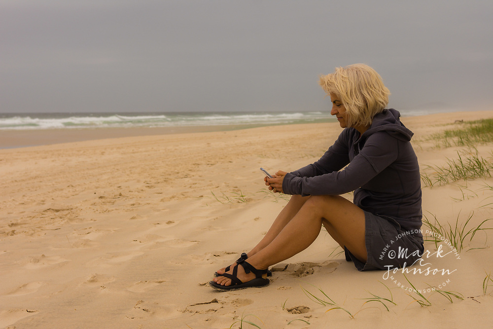 Woman using mobile phone at the beach