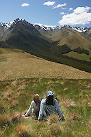 Man and woman sitting in grass looking at mountains back view