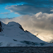 The setting sun catches on snow-covered mountains in  the dramatic Antarctic landscape of Paradise Harbor, Antarctica.