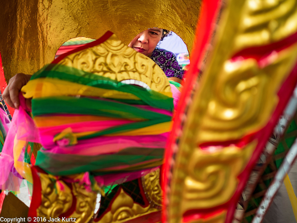30 JANUARY 2016 - NONTHABURI, NONTHABURI, THAILAND: A woman makes merit by leaving blessed scarves at Wat Bua Khwan, a large Buddhist temple in Nonthaburi, north of Bangkok, Thailand.        PHOTO BY JACK KURTZ
