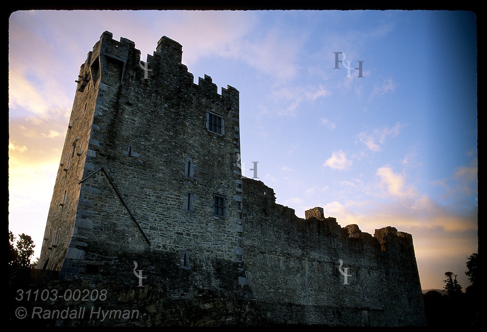 Ross Castle, built by O'Donoghue Ross chieftains in 15th century, looms against dawn sky; Killarney Natl Park, Ireland.