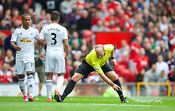 16.08.2014, Old Trafford, Manchester, ENG, Premier League, Manchester United vs Swansea City, 1. Runde, im Bild Referee Mike Dean sprays foam on the pitch // 15054000 during the English Premier League 1st round match between Manchester United and Swansea City AFC at Old Trafford in Manchester, Great Britain on 2014/08/16. EXPA Pictures &copy; 2014, PhotoCredit: EXPA/ Propagandaphoto/ David Rawcliffe<br /> <br /> *****ATTENTION - OUT of ENG, GBR*****
