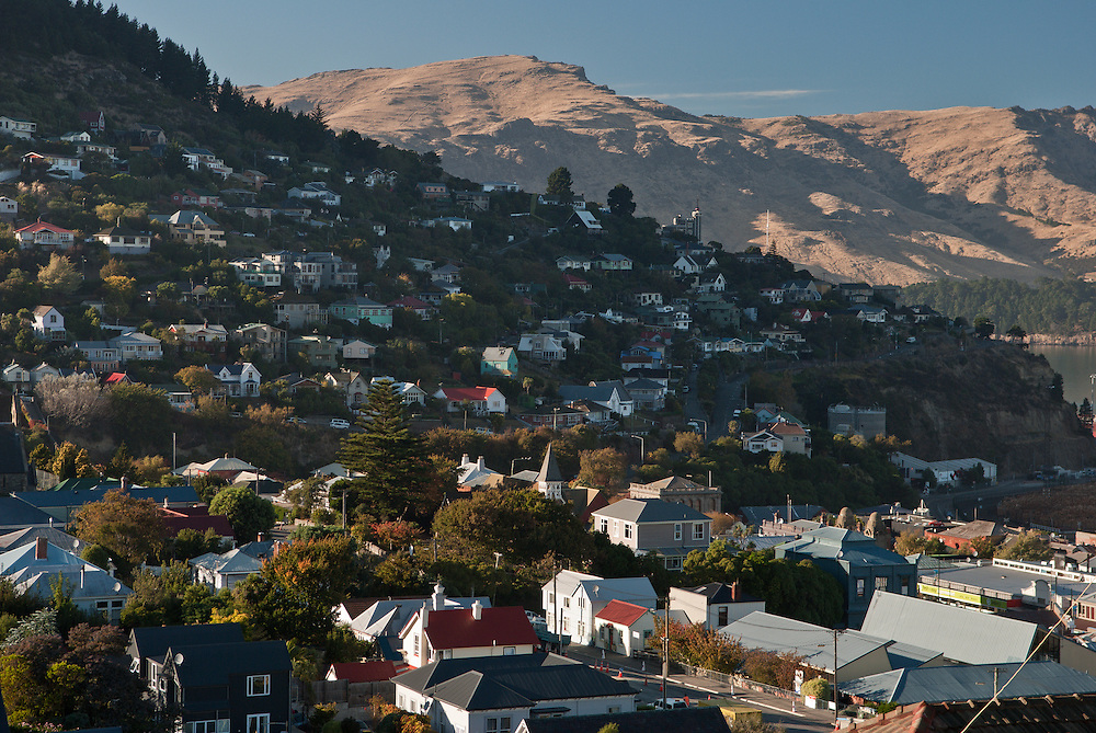 Morning light on Lyttelton houses, picking out the Timeball on the crest of a hill and the Banks Peninsula mountains beyond