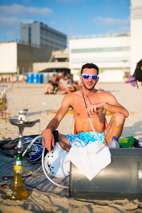 A young Israeli man enjoys a summer day at the beach in Tel Aviv, smoking a water pipe with a large speaker by his feet.
