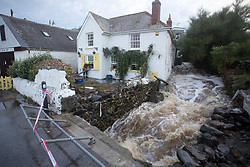 © Licensed to London News Pictures. 18/07/2017. Coverack, UK.  Cornwall Fire and Rescue officers pump out a property after flash floods hit Cornish village of Coverack this afternoon after heavy rainfall.  Photo credit: Ashley Hugo/LNP