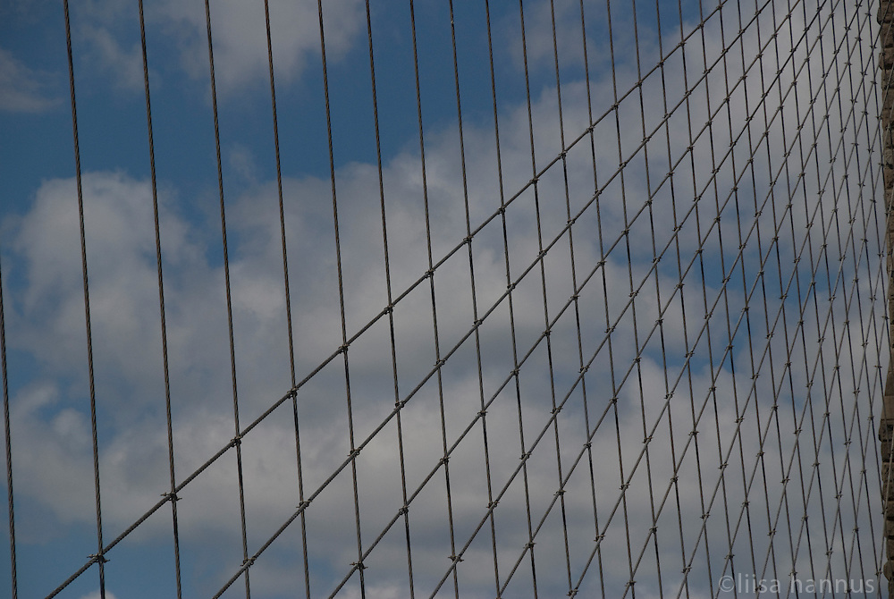 The suspension cables on the Brooklyn Bridge form a geometrica pattern on a summer day in New York City.