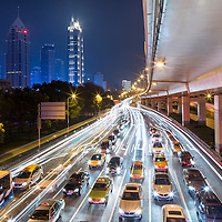 China, Shanghai, Blurred image of car and bus traffic of Yan'an Road beneath concrete overpass on winter evening