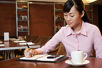 Business woman writing in diary sitting in cafe
