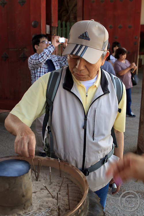 An elderly Japanese man lights an incense stick at the entrance to Todaiji Temple, home to the giant Buddha statue in Nara, Japan.