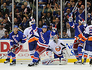 New York Rangers Ryan Callahan (24),  Brandon Dubinsky (17) and Artem Anisimov (42) celebrate Michael Del Zotto's goal against New York Islanders goalie Rick DiPietro during an NHL hockey game Monday, Oct. 11, 2010, in Uniondale, New York. (AP Photo/Kathy Kmonicek)