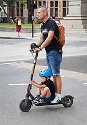 © Licensed to London News Pictures. 28/08/2019. London, UK. A man rides a Xiaomi M365 electric scooter with a small child sitting on the footplate through Parliament Square in London. It is illegal to use an electric scooter in the UK except on private land.  Photo credit: Peter Macdiarmid/LNP