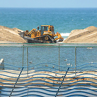 "In preparation for summer, a tractor gathers sand to blocks-up the Pico storm drain on Tuesday, May 29, 2012. ""The Wave Fence"" (part of California Wash: A Memorial) by Newton and Helen Mayer Harrison can be seen in the foreground.."