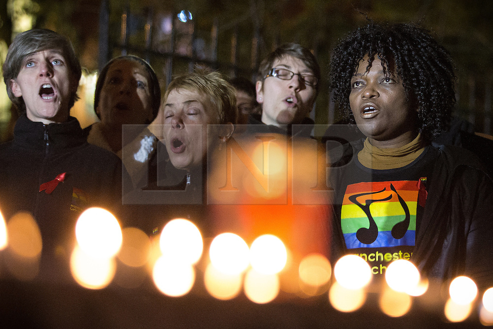 """© Licensed to London News Pictures . 01/12/2013 . Manchester , UK . The Manchester Lesbian and Gay Chorus sing . World AIDS Day commemoration in Sackville Park , Manchester , this evening (Sunday 1st December 2013) including a candle-lit procession around the city's """" Gay Village """" . Photo credit : Joel Goodman/LNP"""