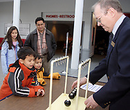 Madelyn, 11, and Oliver Leembruggen watch Nathaniel, 7 and Jameson Leembruggen, 5 (at table) enjoy the Newton's Cradle demonstration during Family Day at the National Museum of the U.S. Air Force, Saturday, January 20, 2007.  Volunteer Don Goodman (right) from Tipp City explains that it operates on principles from Newton's third law of physics.