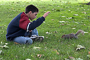 A boy and a squirrel, London UK