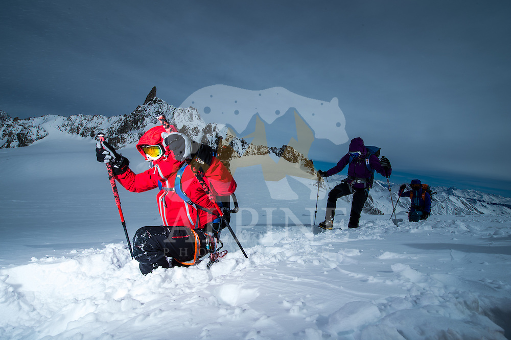 A group of mountaineers as seen struggling with a gusty wind and deep powder snow during a long traverse on Glacier Blanche.