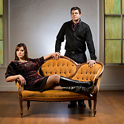 A 20-something-year-old Caucasian couple pose for their engagement portrait session in the Parlour Chapel church in Pittsboro, NC. The woman is sitting in a yellow settee and the man is standing behind her.