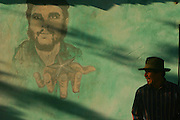 An indigenous man stands in front of a mural depicting leftist and guerilla leader Ernesto Che Guevara in the place where he was captured and killed by Bolivian troops 39 years ago in the village of La Higuera, some 300 southeast of Santa Cruz de la Sierra, Bolivia on Wednesday, June 14, 2006.