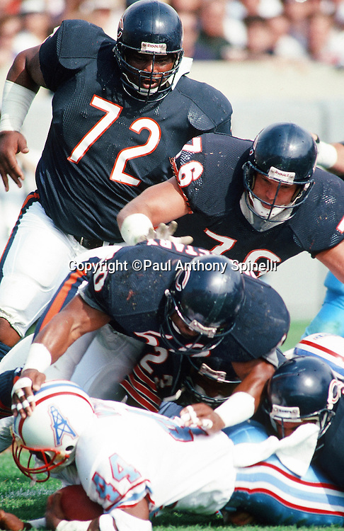 """Chicago Bears defensive lineman William """"Refrigerator"""" Perry (72), Bears defensive lineman Steve McMichael (76), and Bears linebacker Mike Singletary (50) gang Houston Oilers running back Lorenzo White (44) during the NFL football game against the Houston Oilers on Oct. 15, 1989 in Chicago. The Oilers won the game 33-28. (©Paul Anthony Spinelli)"""
