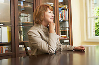 Woman sitting at table in living room