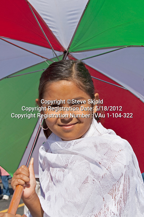 Young Mexican American parade participant carrying multicolored umbrella. Mexican Independence Day Minneapolis Minnesota MN USA