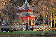 People picnic around the red Chinese Ting Pavilion at Lake Eola Park in Orlando, Florida. Lake Eola Park is located in the heart of Downtown Orlando and home to the Walt Disney Amphitheater.