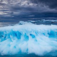 Greenland, Ilulissat, Melting iceberg floating near face of Jakobshavn Isfjord on stormy evening