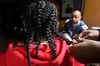 A young man having his cornrows done in the barbers